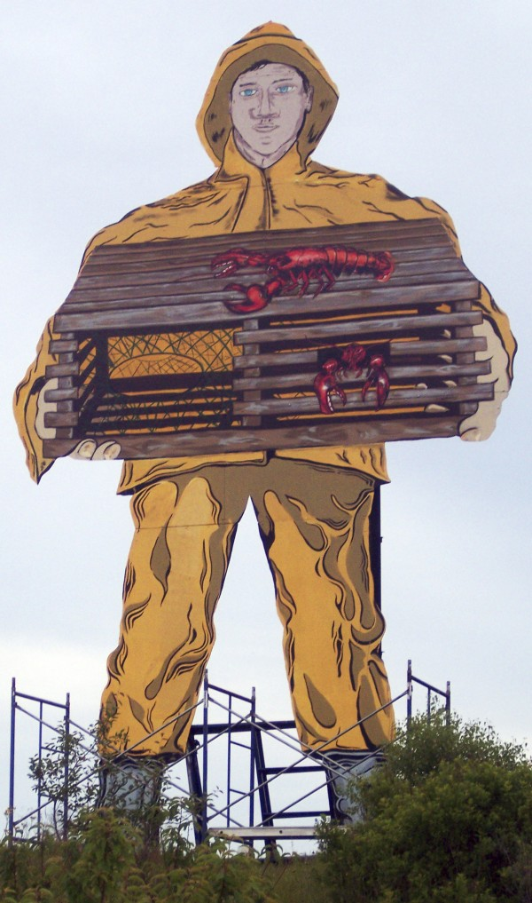 This June 22, 2011, photo provided by the Live Lobster Company shows a billboard-sized aluminum fisherman standing outside what was the last full-time sardine cannery in the U.S. in Gouldsboro, Maine, now holding a lobster trap instead of a tin of sardines.