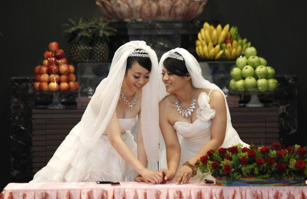 You Ya-ting (left) and her partner Huang Mei-yu stamp their names in front of a statue of Buddha in the prayer hall as they are married in the first Taiwan same sex Buddhist ceremonial wedding in Taoyuan, Taiwan on Saturday, Aug. 11, 2012. Taiwan still does not legally recognize same sex marriage.