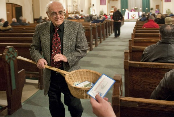 John Alves, of Dartmouth, Mass., uses a basket while taking collection during Mass at St. John the Baptist Roman Catholic Church in New Bedford, Mass., in December 2009. A study on the generosity of Americans, released Monday, Aug. 20, 2012, by the Chronicle of Philanthropy, found that states with populations that are less religious are also the stingiest about giving money to charity.