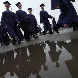 Sidestepping puddles, students march to Alfond Arena to receive their degrees during commencement exercises at the University of Maine in Orono in May.