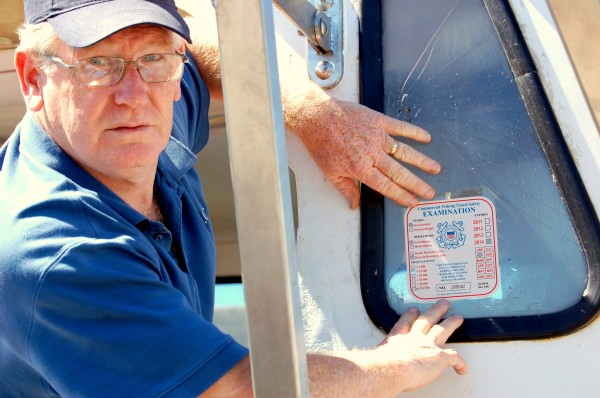 Garry Moores, a commercial fishing vessel safety examiner who works for the U.S. Coast Guard, shows an examination sticker to vessels that pass safety exams like this one affixed to the Nancy Ann, a 40-foot Young Brothers lobster boat skippered out of Jonesport by Ozzie &quotSonny&quot Beal, Jr.