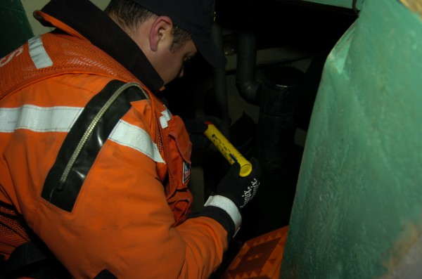 Coast Guard Petty Officer First Class Dave Strickland inspects a flare during a routine vessel safety boarding in January 2007 in Southwest Harbor.