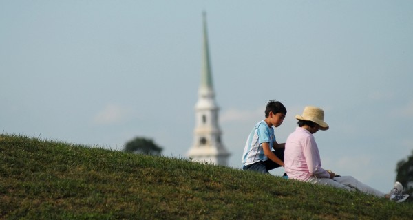 Sandra Tijerina and her son Santiago, 11, take a rest from the American Folk Festival on a hillside by the Dance Pavilion Saturday afternoon, Aug. 25, 2012, in Bangor.