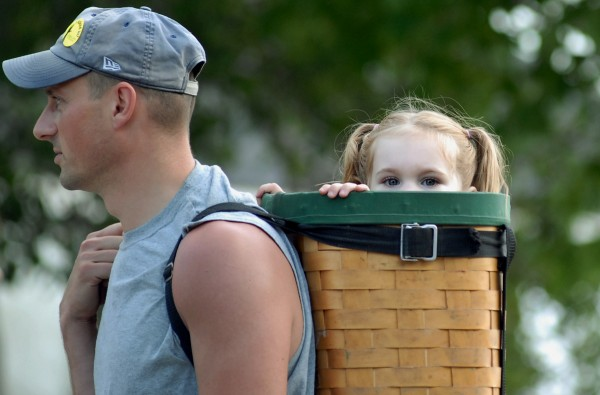Maeve Pelletier, 2, of Orrington peeks out of her dad, Jay's, pack basket as he carries her around the American Folk Festival Saturday afternoon, Aug. 25, 2012.