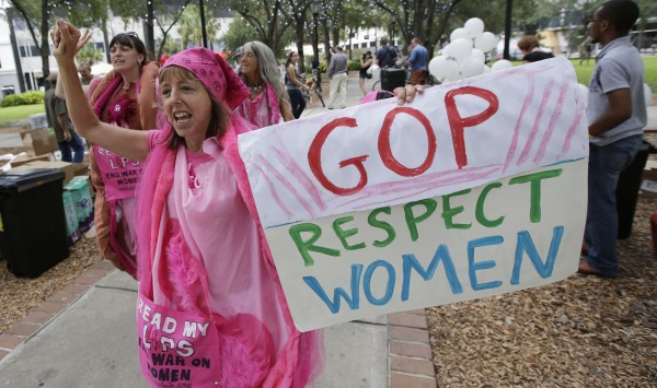 Medea Benjamin of Washington, D.C., displays her sign during a Code Pink protest before Republican National Convention, Sunday, Aug. 26, 2012, in Tampa, Fla.