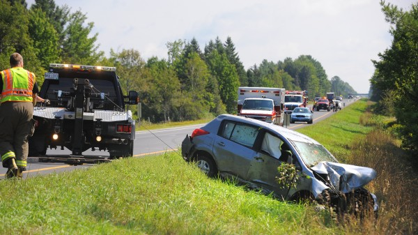 A tow truck pulls a small sedan back onto the roadway after going off the road into trees in the median from the southbound lane of I-95 near mile marker 168 in Etna on Tuesday, Aug. 28, 2012. The female driver was transported to the hospital.