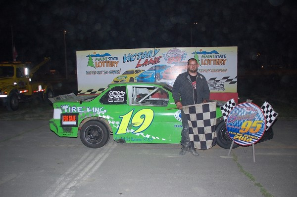 Zach Audet shows off his car in the winners circle after a recent victory at Speedway 95 in Hermon.