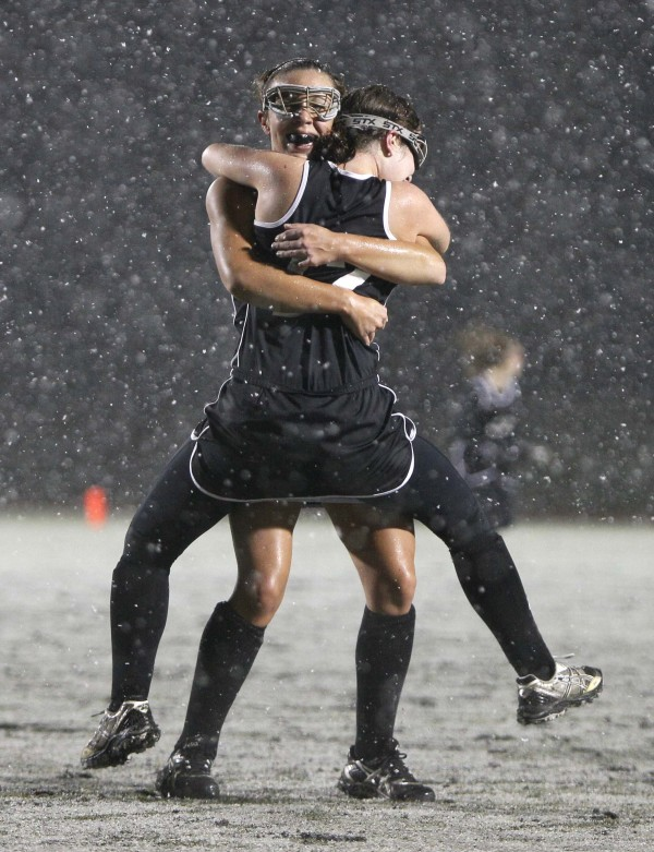 Skowhegan field hockey players Makaela Michonski, (facing camera) embraces teammate Jessica Skillings after their team defeated Marshwood in the snow for the state championship, in Yarmouth on Oct. 29, 2011.