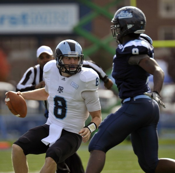 Rhode Island quarterback Steve Probst scrambles away from Maine's Doug Alston during the first half of their game in Orono last season. Rhode Island announced Tuesday that it is remaining as a football member of the Colonial Athletic Association.