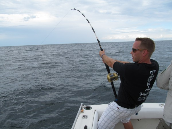 Adam Steck, a prison guard from Buffalo, N.Y., has a blue shark on the line aboard the Atlantic Adventurer on Thursday, Aug. 16, 2012. Steck battled with the shark for more than an hour before the line broke and the shark escaped into the deep.