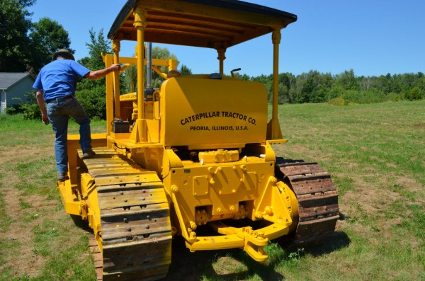 Mike Braley climbs down from his 1939 Caterpillar D7 bulldozer in Pittsfield on Wednesday, Aug. 8, 2012.