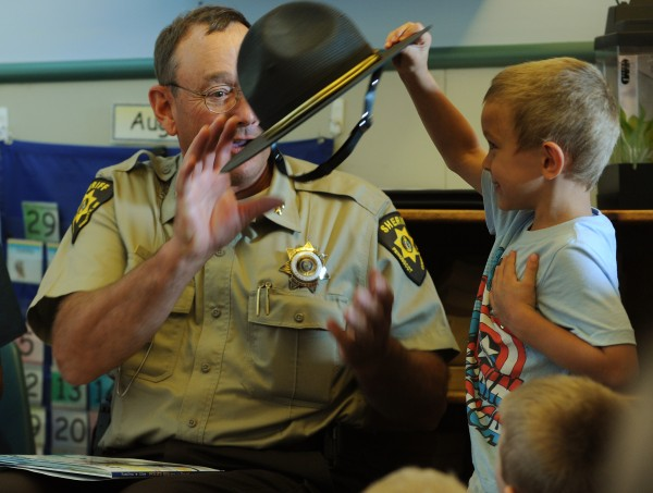 Penobscot County Sheriff Glen Ross gets his hat back from Alexander Kearns after reading to him and other students at the Penquis CAP Head Start Center at the Penobscot Job Corps Academy in Bangor on Tuesday, August 28, 2012. Ross was on hand to promote early education programs that cut crime.