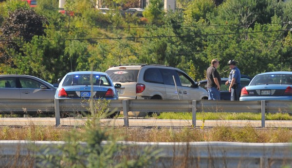 Police cars sorround a minivan that was hijacked and was later stopped on the southbound on ramp from Hogan Road to I-95 in Bangor on Friday, Aug. 24, 2012.