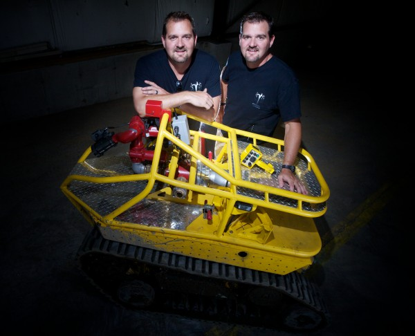 Mike and Geoff Howe of Howe and Howe Technologies stand with their unmanned robotic firefighting machine, known as the Thermite, at their headquarters in Waterboro Monday, Aug. 13, 2012.