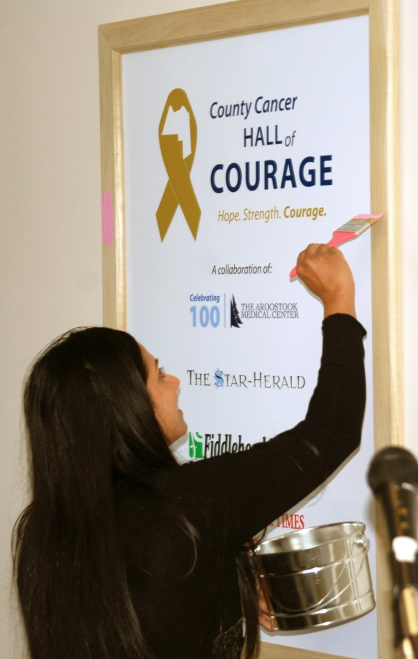 Dr. Vatsala Kirtani of The Aroostook Medical Center''s Aroostook Cancer Care participates in the official launch of the County Cancer Hall of Courage by applying pink paint on the first frame that will feature a yet-to-be-named breast cancer survivor. The official opening for the County Cancer Hall of Courage will take place in early October when the first featured cancer survivor story and photo will be unveiled in the pink frame.