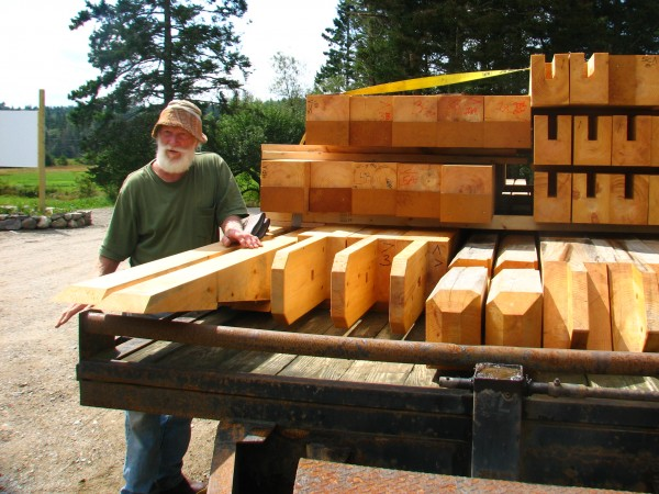 Bill Thayer of Darthia Farm in Gouldsboro stands Tuesday, Aug. 28, 2012, next to a trailer stacked with timbers that will be used in the farm's new barn. The new structure will replace a 153-year-old timber-framed barn that burned to the ground in May, killing dozens of animals inside.
