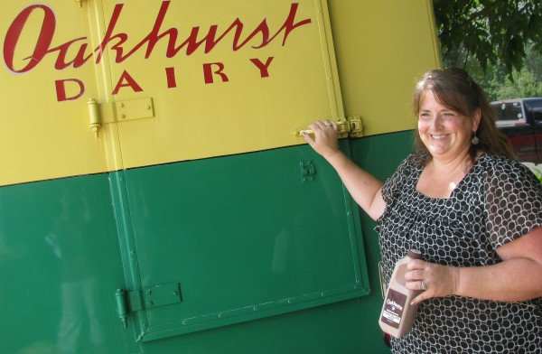 Oakhurst Dairy contest winner Robin Roberts Webster poses in Morrill on Tuesday afternoon, Aug. 14, 2012 near the vintage delivery van that brought her the first installment of her prize of milk for life.