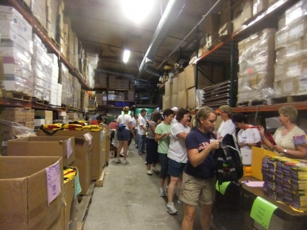 Dozens of Ruth's Reusable Resources volunteers and workers help stuff backpacks in the nonprofit organization's Portland warehouse. This is the busiest time of year for the organization, which annually donates hundreds of backpacks filled with school supplies to schools all over Maine.