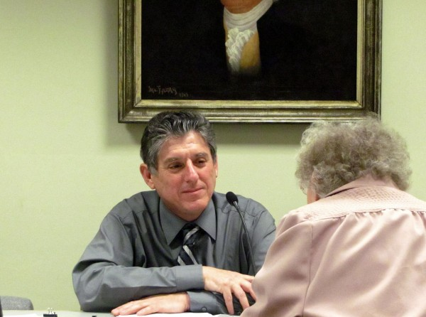Roger Raymond talks to a longtime resident in Bucksport's town office in April 2012, during Raymond's final meeting as town manager.