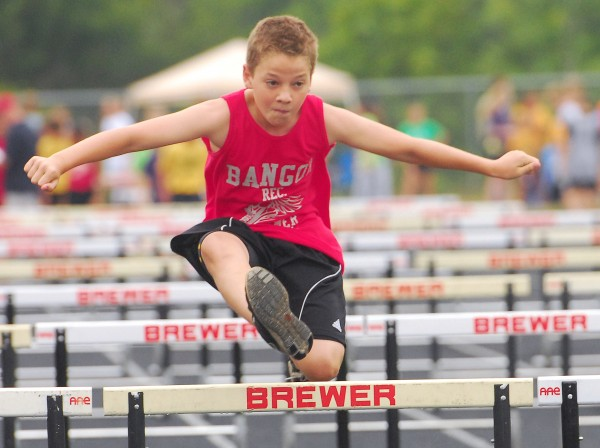 Conor O'Brien of Bangor clears the last hurdle in the Midget 80- meter hurdles at the youth state track and field championships held at Brewer Community School Sunday, Aug. 12 2012.