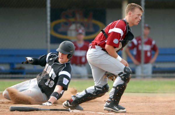 Ryan Angelico of the U.S. East team from Auburn, Mass., slides into home by Maine District 3 catcher Michael Ward in the 2nd inning of the Senior Little League World Series game Tuesday evening at Mansfield Stadium in Bangor.  U.S. East won the game 11-0.