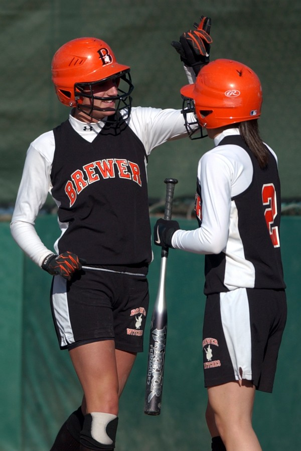 Brewer's Sarah Estes (left) celebrates with teammate Dominique Defilipp after scoring a run during a high school softball game in 2006. Estes has been named Old Town High School's new field hockey coach.