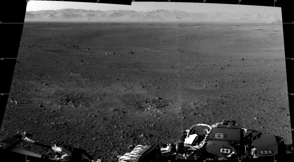 These are the first two full-resolution images of the Martian surface from the Navigation cameras on NASA's Curiosity rover, which are located on the rover's &quothead&quot or mast. The rim of Gale Crater can be seen in the distance beyond the pebbly ground. The topography of the rim is very mountainous due to erosion. The ground seen in the middle shows low-relief scarps and plains. The foreground shows two distinct zones of excavation likely carved out by blasts from the rover's descent stage thrusters.