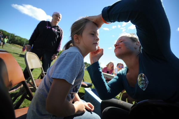 Volunteer Maegan Sanders (right) of Bangor Youth Cheering applies face paint to Kelsey Moulton, 7, as her mom Shannon Eberhart (in background, on left) looks on. The Bangor Housing Authority held its end-of-summer block party at Downeast Elementary School Wednesday, Aug. 29, 2012.