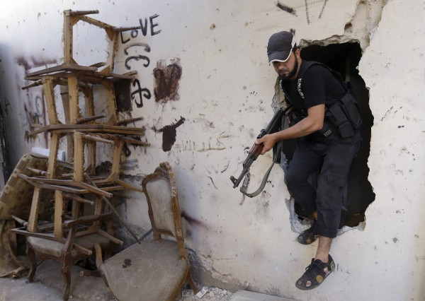 A Sunni gunman steps out from a hole made by fighters to move from street to street during clashes that erupted between supporters and opponents of the Syrian regime in the northern port city of Tripoli, Lebanon, on Wednesday, Aug. 22, 2012.