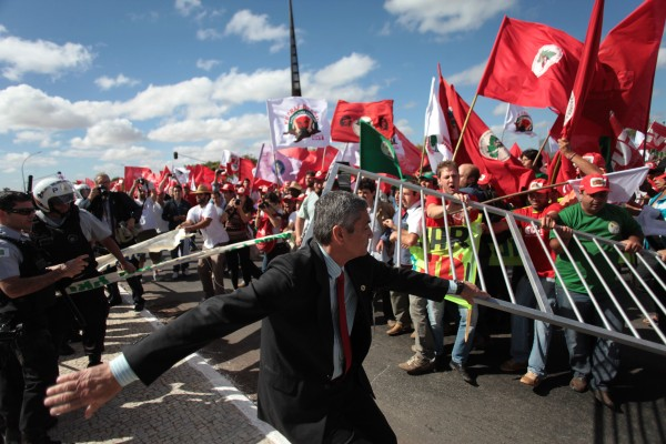 Rural workers clash with police officers and security agents in front of the Planalto presidential palace in Brasilia, Brazil, on Wednesday, Aug. 22, 2012. According to officials, more than 5,000 representatives of rural social movements participated in a protest march to the presidential palace demanding the government resolve the country''s agrarian problems, including the demarcation of indigenous lands and financing for small family farms.