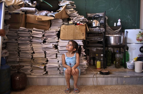 Sana Mustafa, 5, of Syria, who fled her home in Anadan with her family due to fighting between the rebels and the Syrian army, talks with her brother Riyyad in a school where she and her family took refuge, in Kafar Hamra, on the outskirts of Aleppo, Syria, on Wednesday, Aug. 22, 2012.