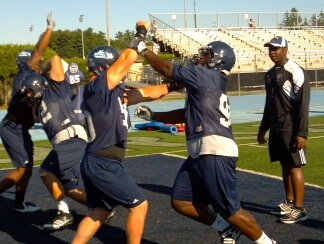 University of Maine defensive linemen David Toriola (right) and Matt Pellerin work on their technique under the watchful eye of assistant coach Dennis Dottin-Carter during Friday's practice on Morse Field at Alfond Stadium. The duo is expected to help shore up the middle of the line this season.