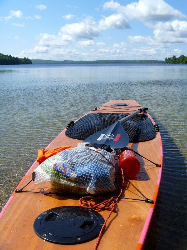 A wooden stand-up paddle board is loaded with gear and sits on the shore of Cold Stream Pond in Penobscot County, Maine, in June 2012. The Little Vessels paddle board was handcrafted by its owner, Bar Harbor native Amanda James, and she is using the board for her &quot100 Maine Lakes&quot project, a mission to cross Maine's 100 largest lakes.
