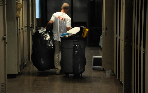 A participant in Penobscot County's alternative OUI sentencing program removes trash and other items from the old Hampden Academy Saturday morning, Aug. 11, 2012.