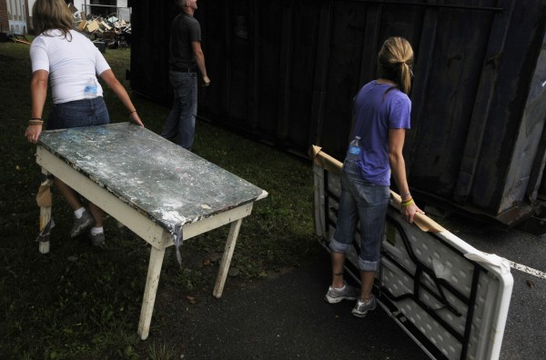 Participants in Penobscot County's alternative OUI sentencing program work with Hampden Academy staff to remove furniture, trash and other items from the old Hampden Academy on Saturday, Aug. 11, 2012.