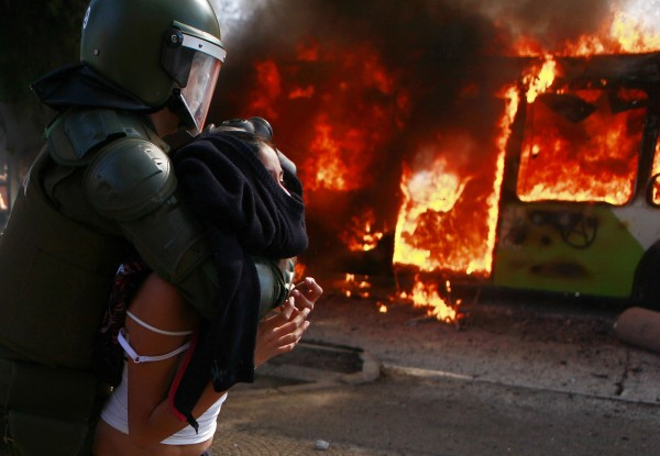 A young woman is taken away by riot police as a public bus burns during clashes between students demanding free education and riot police in Santiago, Chile on Wednesday, Aug. 8, 2012. Police used water cannons and tear gas to break up the protest and three buses were set ablaze.