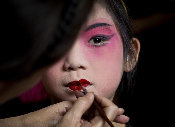 A girl is applied makeup before a training at Peking Opera summer camp organized by the Peking Opera House in Beijing, China on Tuesday, Aug. 14, 2012. The summer training course was held to attract the public to Chinese traditional performance.
