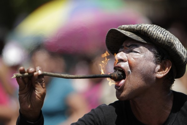 A man who is known by his nickname &quotFlama,&quot or &quotFlame,&quot performs with fire during a parade marking the start of celebrations in honor of the capital's patron Saint, Divino Salvador del Mundo, or Divine Savior of the World, in San Salvador, El Salvador on Wednesday, Aug. 1, 2012. The statue of the saint, which sits in the Sacred Heart Basilica, will be paraded through the streets to the Cathedral and back on Monday, Aug. 6, the patron saint's day.