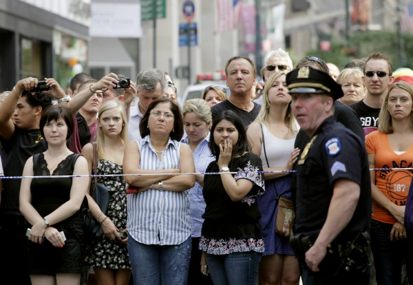 Bystanders and a police officer stand on Fifth Avenue to view the scene after a multiple shooting outside the Empire State Building on Friday, Aug. 24, 2012, in New York. At least four people were shot on Friday morning and the gunman was dead, New York City officials said. A witness said the gunman was firing indiscriminately. Police said as many as 10 people were injured, but it is unclear how many were hit by bullets. A law enforcement official said the shooting was related to a workplace dispute. The official spoke on condition of anonymity because the investigation was ongoing.