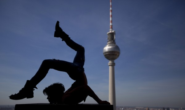 Spanish acrobat David Pereira is silhouetted as he performs on the roof terrace of a hotel with the 368 meters high television tower in the background during a photo call in Berlin, Germany on Wednesday, Aug. 1, 2012. Pereira and other artists presented parts of the new show &quotMade in Berlin&quot of the Wintergarten Berlin Variety, which will premiere Aug. 9, 2012.