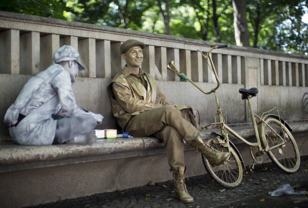 Mime artists Maciek (right) and Viola painted in gold and silver take a break in the shade, near the Brandenburg Gate in Berlin, Germany on Wednesday, Aug. 1, 2012. The Polish street artists used to perform in front of the landmark.