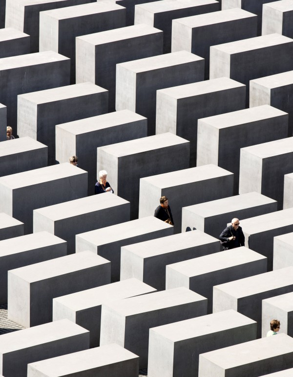 People walk through the concrete blocks of the the Holocaust memorial in Berlin, Germany on Monday, Aug. 13, 2012. The memorial to the 6 million Jews killed in Europe under the Nazis was created by U.S. architect Peter Eisenman and consists of an undulating field of 2,711 blocks through which visitors can wander.