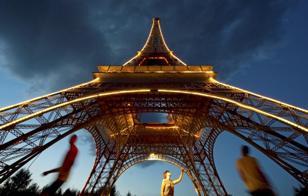 People walk beside an illuminated model of the Eiffel Tower in the landscape park Miniwelt (Miniworld) during the sunset in Lichtenstein, eastern Germany, Wednesday, Aug. 29, 2012. The cultural park Miniworld presents about 100 original and true-to detail buildings and technical facilities at a 1:25 scale ranging on an area of 6.5 hectares. All buildings invite the visitors to take a walk through the last 3,500 years of building history, moving from the ancient world to present.
