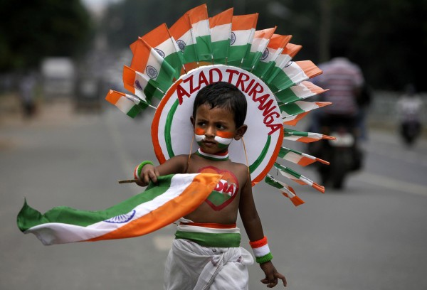 A young Indian child carries the Indian flag as he takes part in a street play during rehearsal for the Indian Independence Day celebrations in the eastern Indian city Bhubaneswar, India on Tuesday, Aug. 14, 2012. India celebrates its 1947 independence from British colonial rule on Aug. 15.