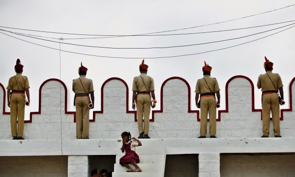 Members of police wait with their trumpets to perform as a school girl sits on steps during a gathering on the occasion of 65th anniversary of India's independence from British rule, in Bangalore, India on Wednesday, Aug. 15, 2012.