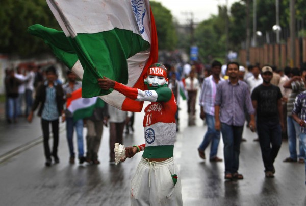 An Indian cricket fan with his body painted in national flag colors waves a national flag outside the stadium before the start of fourth day's play of the first cricket test match between India and New Zealand in Hyderabad, India on Sunday, Aug. 26, 2012.