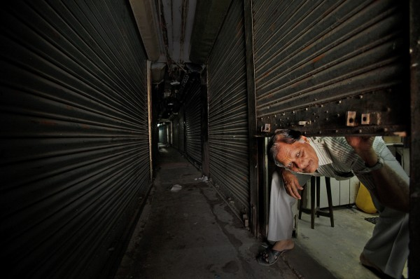 A shopkeeper looks out from inside a closed shop during a 12-hour general strike called by radical Hindu group Bajrang Dal in Gauhati, Assam state, India on Monday, Aug. 27, 2012. The strike was to protest the recent ethnic violence in the state which killed at least 80 people and displaced 400,000. Bajrang Dal also demanded sealing of the India Bangladesh border to stop the ongoing violence.