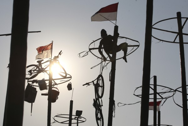 Indonesian men participate in a greased pole climbing competition held as part of independence day celebration on Ancol beach in Jakarta, Indonesia on Friday, Aug. 17, 2012. Contestants race up to grab items ranging from buckets to bicycles hanging from the top of the poles as prize. Indonesia is celebrating its 67th anniversary of independence from the Netherlands.
