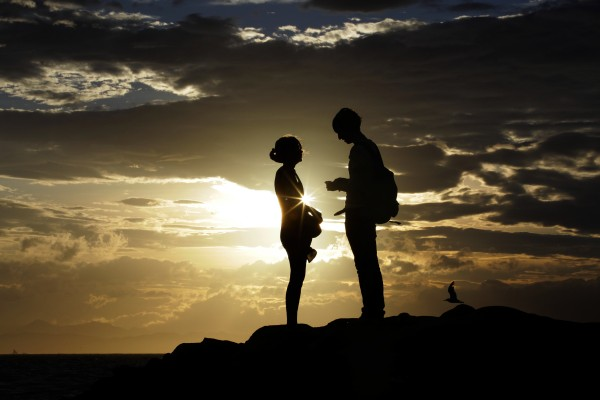 A couple talks with each other as the sun sets at Enoshima beach in Fujisawa, near Tokyo on Wednesday, Aug. 15, 2012.