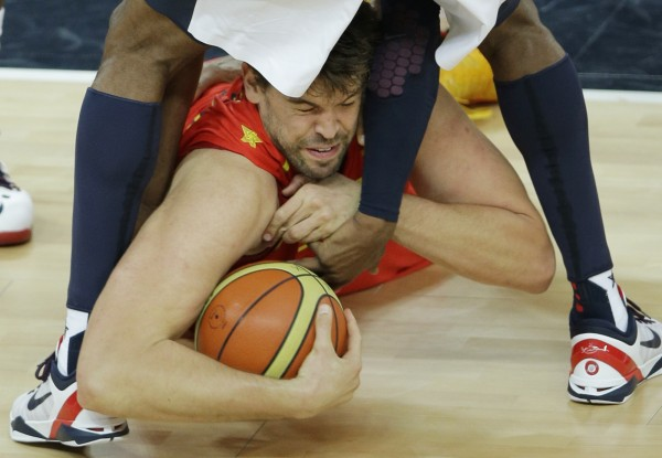 Spain's Marc Gasol dives at the feet of United States' Kobe Bryant for the basketball during the men's gold medal basketball game at the 2012 Summer Olympics, Sunday, Aug. 12, 2012, in London.